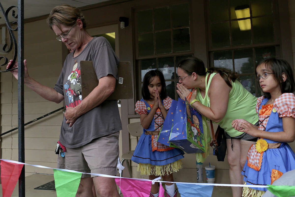 Elizabeth Briggs prays with her twin daughters, Noor, center, and Yasmeen to kick off Fall Fest at First Baptist Church of Sutherland Springs on Oct. 31, 2018. At left is Nish Harris.