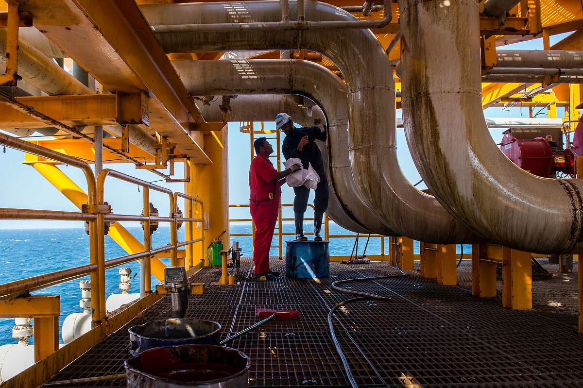Workers clean oil leaks from pipes aboard an offshore oil platform in the Persian Gulf's Salman Oil Field, operated by the National Iranian Offshore Oil Co., near Lavan island, Iran, on Thursday, Jan. 5. 2017. NEXT: Continue to see the world's largest refineries.