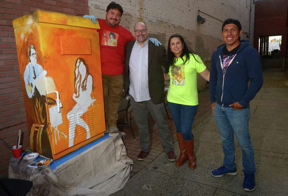 Artist Cesar Alvarez, Factory Underground Director of Marketing & Publicity Marc Alan, Milena Alvarez and Rene Soto of Rene Soto Gallery, pose for a photo as Alvaraez paints a utility box on the sidewalk outside the Wall Street Theater on Wall Street Thursday, November 1, 2018, in Norwalk, Conn. The Norwalk Arts Commission commissioned the Greenwich artist to paint the electric box next to Wall Street Theater as part of their intiative to help beautify the city . Photo: Erik Trautmann / Hearst Connecticut Media / Norwalk Hour
