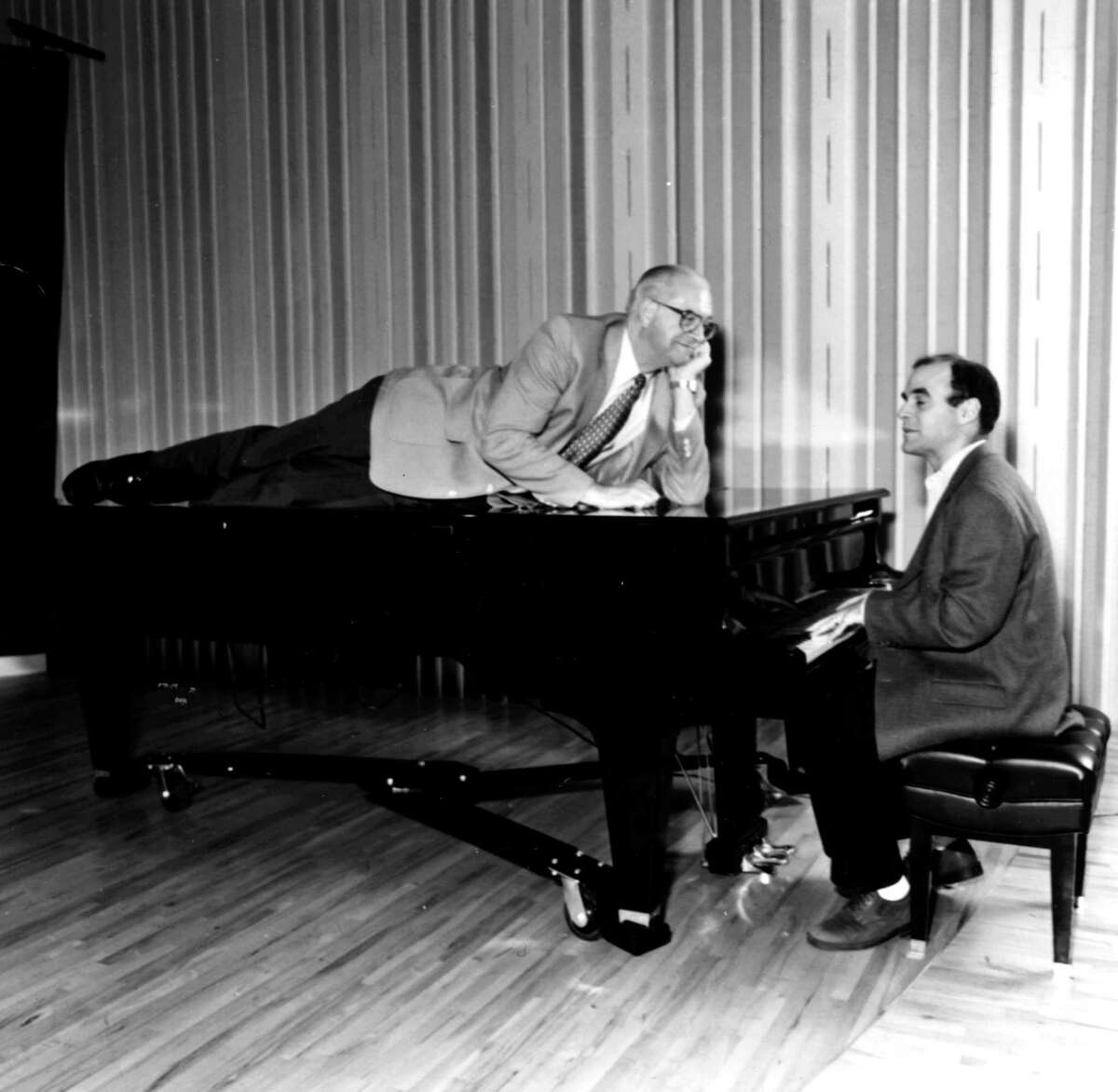 """Carl Kasell, reclining on the piano, and Peter Sagal in an early """"Wait Wait ... Don't Tell Me!"""" promotional photo."""