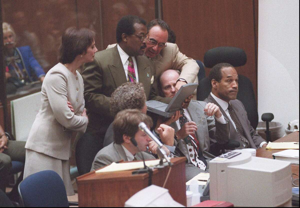 Prosecutor Marcia Clark looks over the shoulders of defense attorneys Johnnie Cochran Jr., center, and Robert Shapiro as they review the records relating to the shoe prints found in the Ford Bronco and at the murder scene, during closing arguements in the O.J. Simpson double-murder trial, Tuesday, Sept. 26, 1995, in Los Angeles. (AP Photo/Myung J. Chun, Pool)