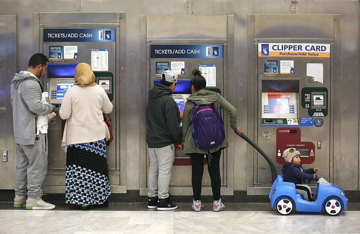 In this file photo, BART commuters including Francisco Mendoza (middle) with her sister Carmelina Mendoza (middle right) with her 1 year old child Michael (right) buy tickets to go to Oakland at the Civic Center station on Tuesday, April 10, 2018, in San Francisco, Calif.