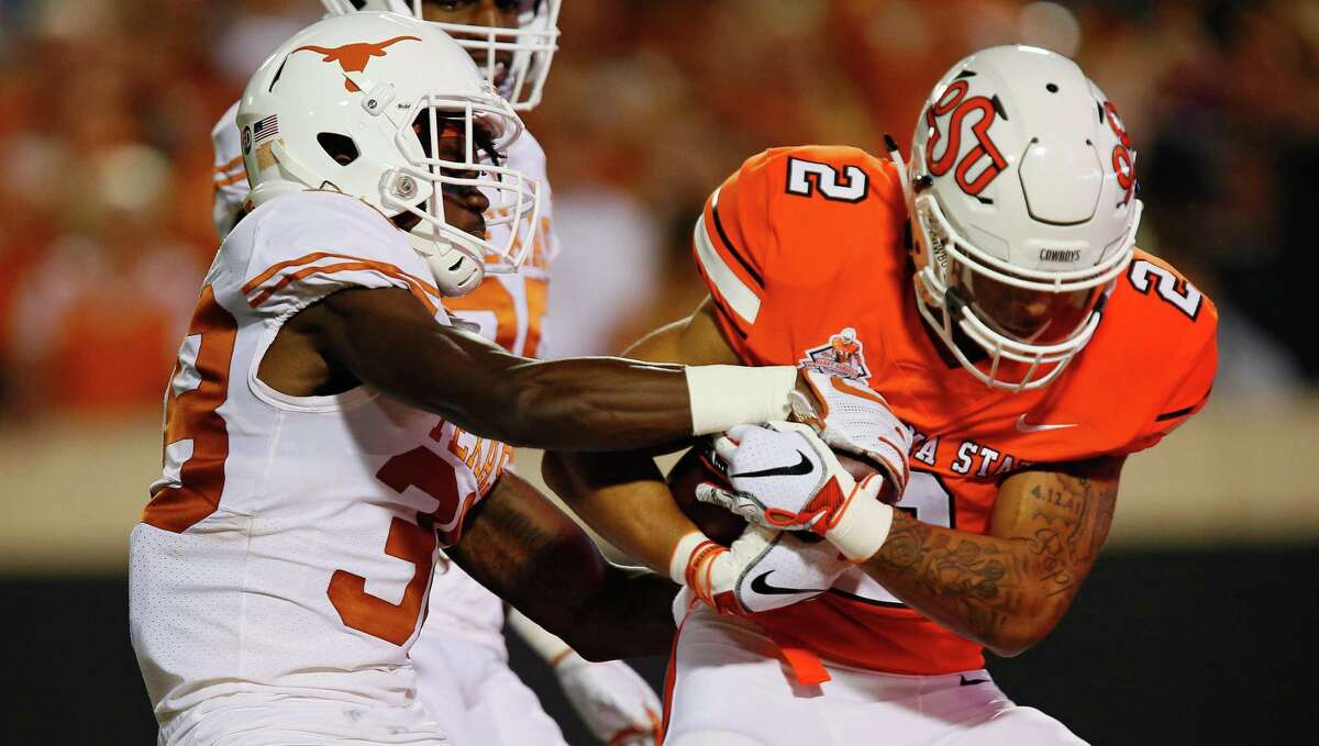 Kobe Bryce, trying to strip the ball from Oklahoma State's Tylan Wallace last season, has emerged as a starting cornerback for the Longhorns.