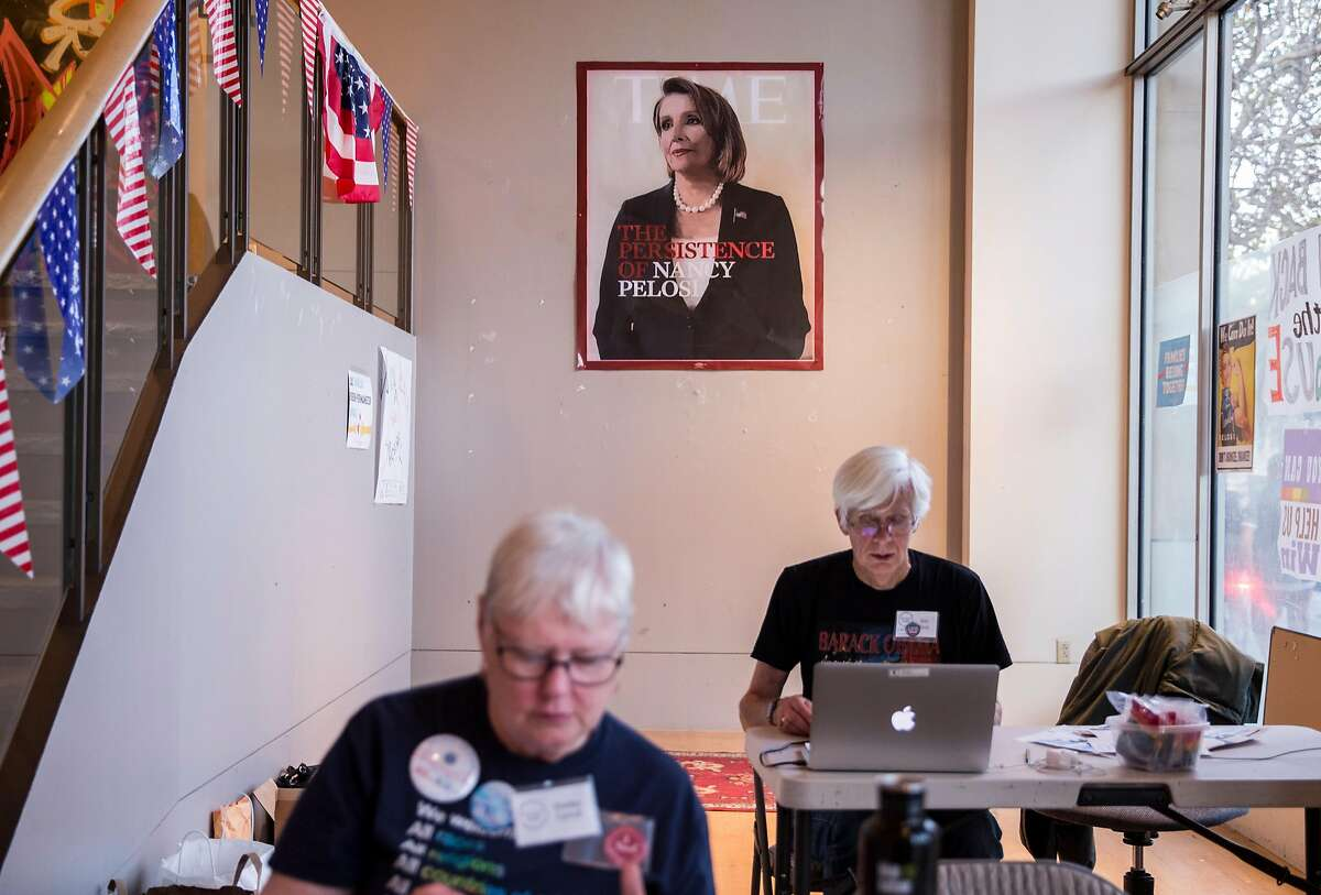 Two volunteers man the front door while sitting under a painted replica portrait of House Minority Leader Nancy Pelosi at the Red to Blue campaign office established by Pelosi in San Francisco, Calif. Thursday, Nov. 1, 2018.