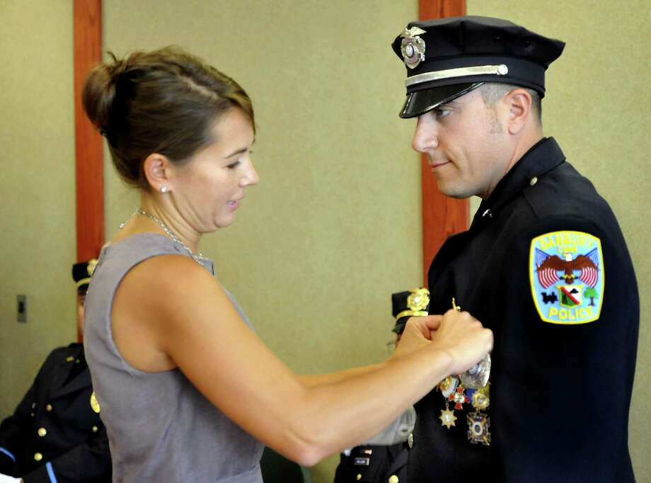 Tanya LaBonia performs the traditional pinning ceremony as her husband, Len LaBonia, is promoted to detective in the Danbury Police Department Thursday, Sept. 15, 2011. Photo: Michael Duffy / Michael Duffy / The News-Times