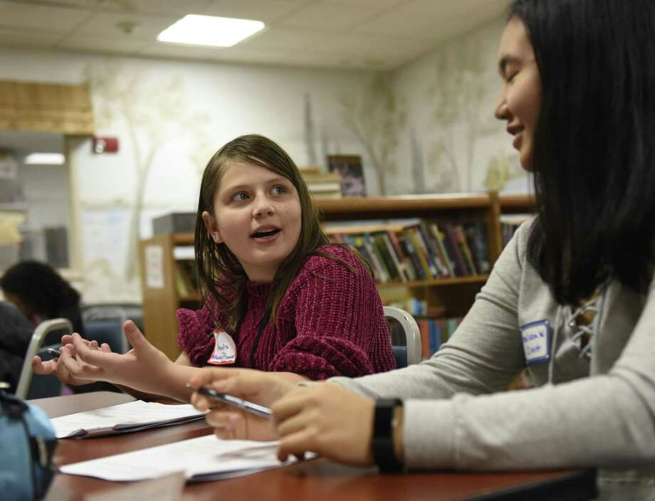 Kendra Bobes, left, explains her money management plan to GHS Economics Club member Melissa Woo during the My Money Planning Program at the Boys & Girls Club in Greenwich Thursday. Nov. 1, 2018. Sponsored by the Greenwich United Way, the six-week program helps kids learn valuable money management and saving skills culminating with a celebration of skills on Dec. 13. Photo: Tyler Sizemore / Hearst Connecticut Media / Greenwich Time