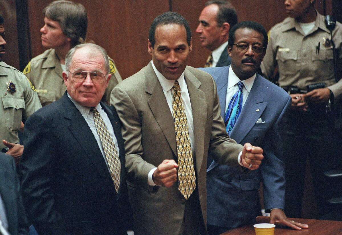 O.J. Simpson, center, reacts as he is found not guilty of murdering his ex-wife Nicole Brown and her friend Ron Goldman in Los Angeles, in this Oct. 3, 1995 file photo. The former football star stands between members of his defense team, F. Lee Bailey, left, and Johnnie Cochran Jr. The Simpson trial is the focus of the PBS