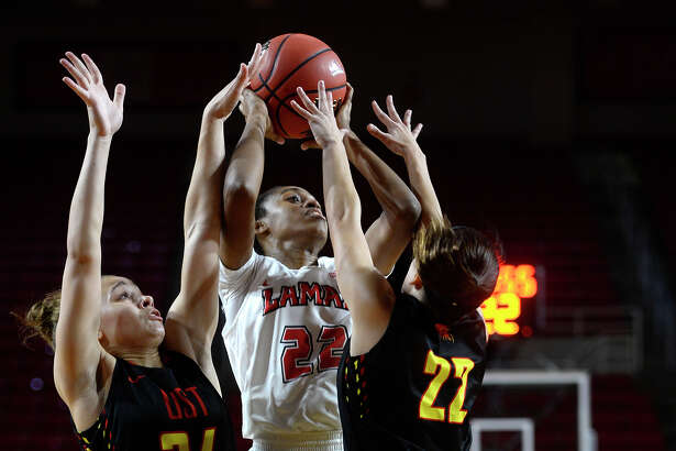 Lamar guard DeA'ngela Mathis goes in for a layup against defenders Sheridan Hopkins, left, and Tori Frederick during the home opener against St. Thomas on Wednesday evening. Photo taken Wednesday 11/16/16 Ryan Pelham/The Enterprise
