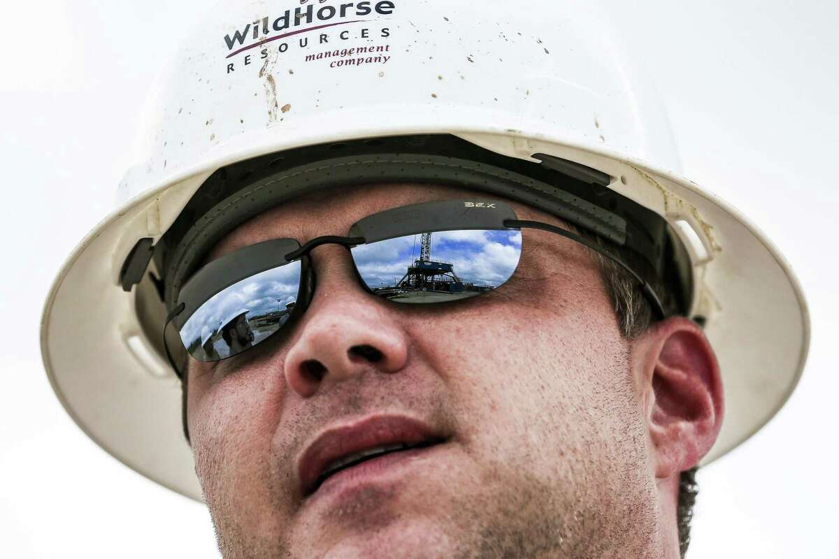 A drilling rig is reflected in the glasses of WildHorse Resource Development drilling superintendent Josh Bradford outside Caldwell Tuesday Oct. 2, 2018. The WildHorse oil and gas operations lie on the northeastern edge of the Eagle Ford Shale, which is seeing a modest rebound in production after the recent oil bust. (Michael Ciaglo/Houston Chronicle via AP)