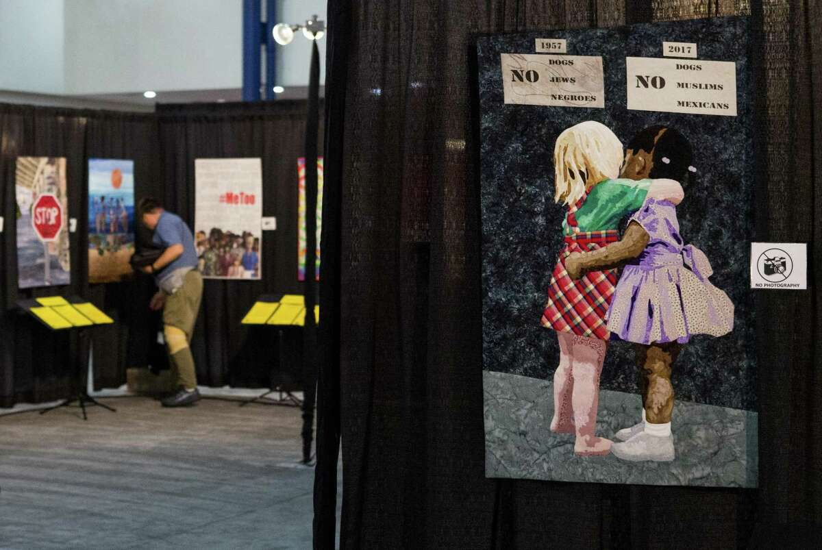 """Harmon Everett walks through the OURstory exhibit as he helps set up of the 2018 International Quilt Festival at the George R. Brown Convention Center. The quilt titled """"Color Blind,"""" in the foreground, is part of the powerful OURstory exhibit that tackles human rights subjects through art quilts."""