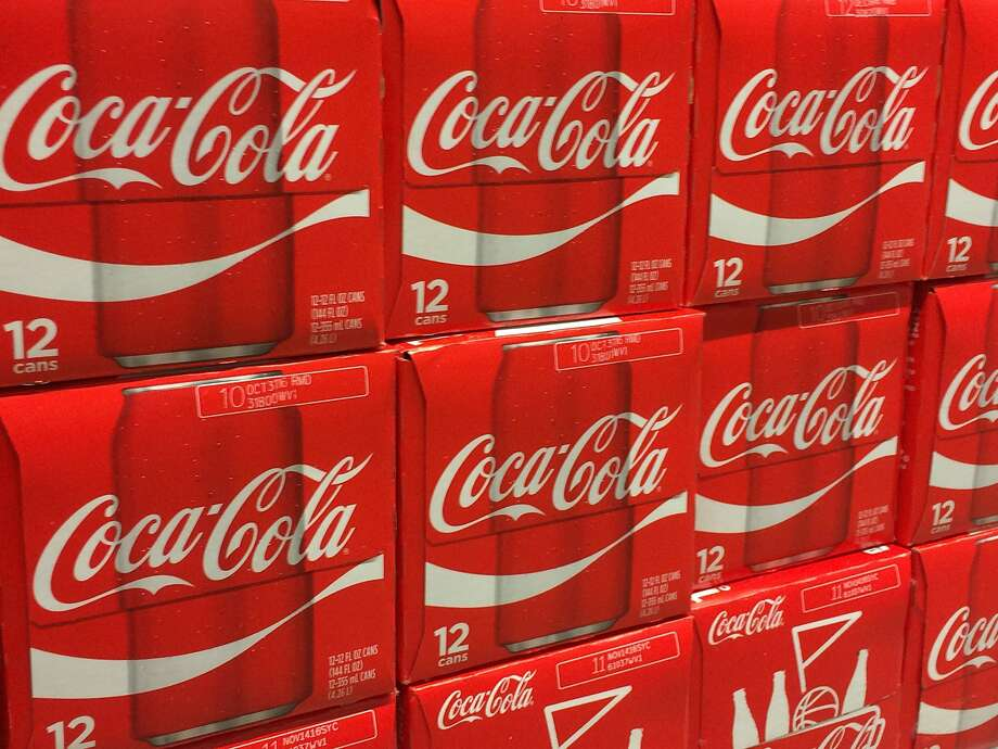 (FILES) In this file photo taken on April 30, 2016 cases of Coca-Colaare seen on a grocery shelf in Gainesville, Virgina. - Coca-Cola reported a jump in third-quarter profits behind higher sales in North America as it boosts investment in non-carbonated beverages on October 30, 2018. The soda giant notched profits of $1.9 billion, up 30 percent from the year-ago period. Revenues fell 9.2 percent to $8.2 billion.Sales surged 12 percent in North America, with Coca-Cola pointing to pricing increases, especially in sparkling soft drinks, offset somewhat by higher shipping costs. (Photo by Karen BLEIER / AFP)KAREN BLEIER/AFP/Getty Images Photo: KAREN BLEIER, AFP/Getty Images