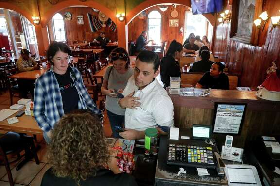 Ivan Sanchez, from right, Jane Lesnizk and Rebecca Shukla order food for a get-out-the-vote rally the next day, at aqueira Mexico Lindo Friday, Nov. 2, 2018, in Houston.