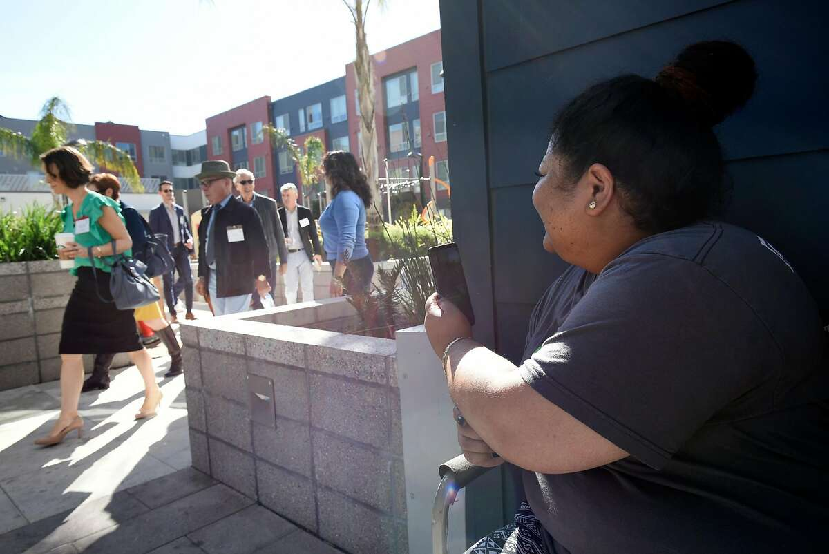 Resident Baby Olomua takes a video with her phone of dignitaries walking by before the start of a dedication ceremony for the new Alice Griffith Houses development in San Francisco, CA, on Friday November 2, 2018.