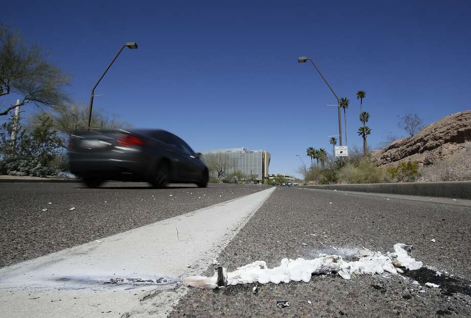 A vehicle goes by the scene of a fatality where a pedestrian was stuck by an Uber vehicle in autonomous mode, in Tempe, Ariz in March 2018. Photo: Chris Carlson / Associated Press 2018