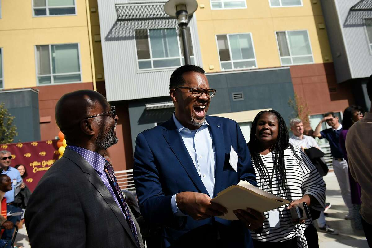 Fred Blackwell, CEO of HOPE SF, , center, shares a laugh with James McCray, Executive Director of Tabernacle Community Development Corp., during a dedication ceremony for the new Alice Griffith Houses development in San Francisco, CA, on Friday November 2, 2018.