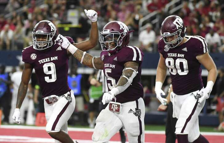 Texas A&M running back Trayveon Williams (5) celebrates his touchdown run against Arkansas with wide receiver Hezekiah Jones (9) and tight end Trevor Wood (80) during the fourth quarter of an NCAA college football game Saturday, Sept. 29, 2018, in Arlington, Texas. (AP Photo/Jeffrey McWhorter)