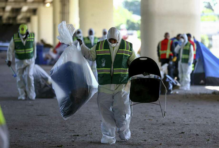 Solid Waste and Health Department employees move items that will be put in storage for people who lived at the Wheeler homeless encampment and are waiting housing employees Friday, Nov. 2, 2018, in Houston. The area where the encampment was located will be used as bus parking lot. City of Houston personnel, The Way Home coalition and the Texas Department of Transportation provided free transportation to shelters for residents of the encampment. Photo: Godofredo A. Vasquez, Houston Chronicle / Staff Photographer / 2018 Houston Chronicle