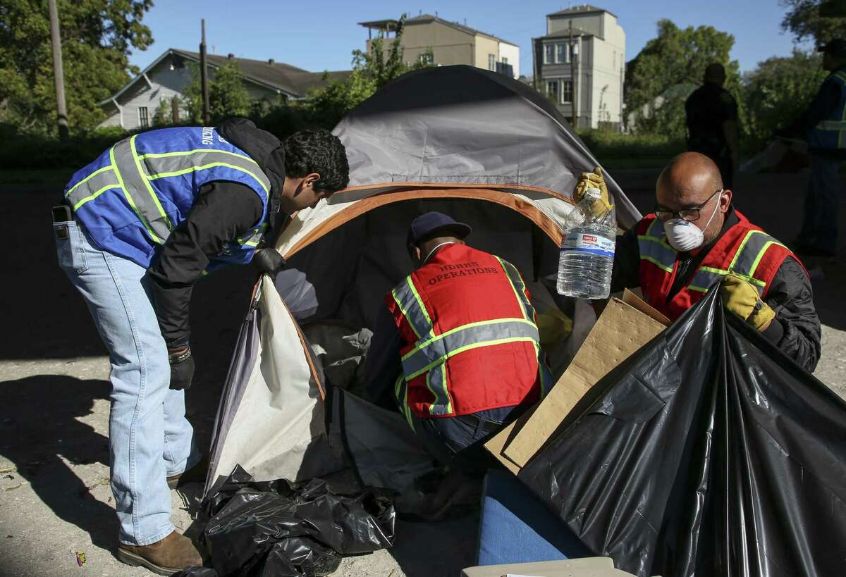 Solid Waste and Health Department employees vacate a tent that was left at the Wheeler homeless encampment Friday, Nov. 2, 2018, in Houston. The area where the encampment was located will be used as bus parking lot.
