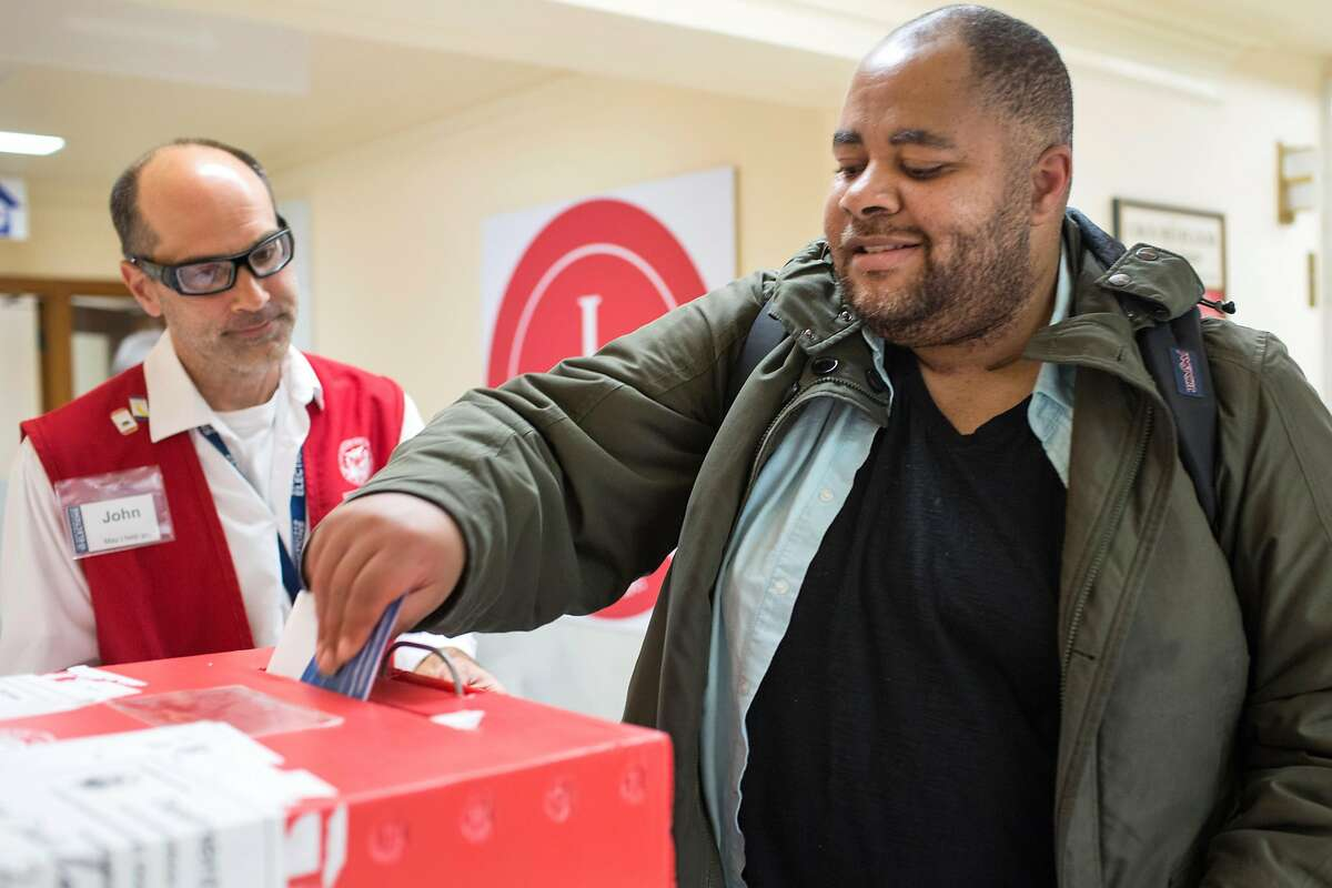 Tony Page, who is currently homeless, casts his vote at City Hall with the assistance of John Silmser (left), voter services representative. Page participated in the procession led by Melanie DeMore to come to vote on Saturday, October 27, 2018 in San Francisco, Calif.
