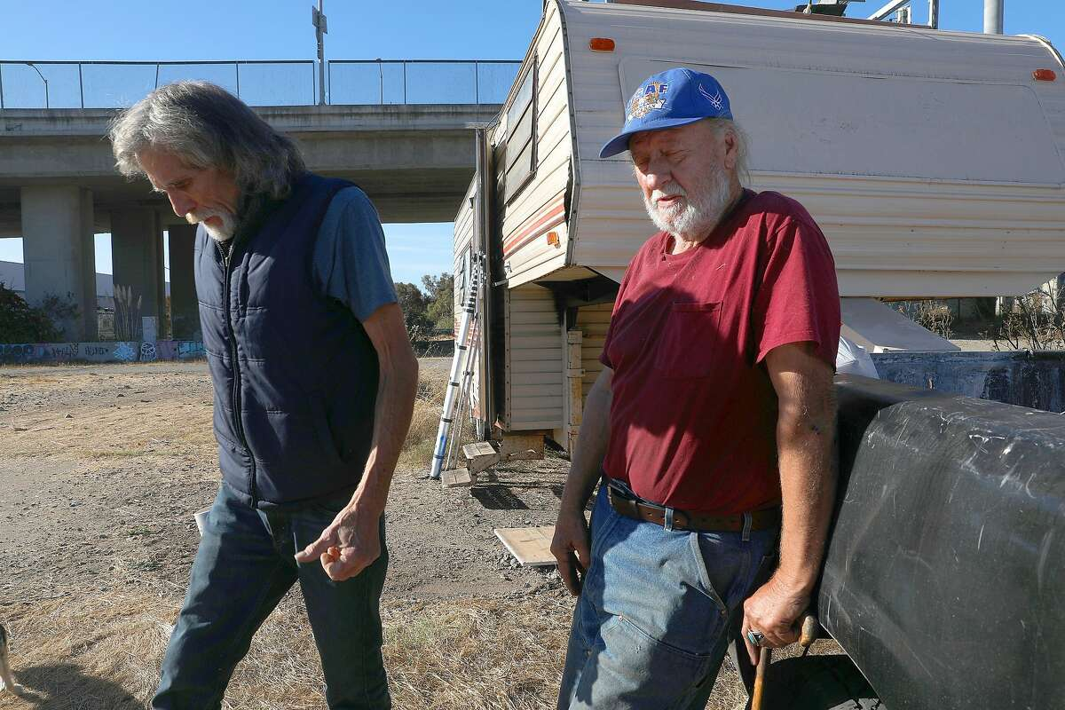 Kelly Thompson (right) stands by his RV and truck which was towed last week on Friday, Nov. 2, 2018, in Oakland, Calif. Gary Rosenquist, who lives in a bus, helped Thompson with the cost of getting his truck back. The Oakland City Council voted to open four RV sites in the city that will provide up to 150 RVs with secure parking, sanitary facilities and garbage services.
