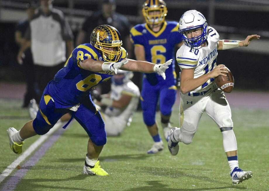 Newtown quarterback Luke Melillo (10) stays out of the grasp of Brookfield's Gavin Borges (83) as he scrambles out of the backfield in the football game between Newtown and Brookfield high schools, Friday night, November 2, 2018, at Brookfield High School, Brookfield, Conn. Photo: H John Voorhees III / Hearst Connecticut Media / The News-Times
