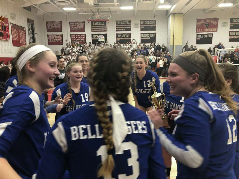 East Hampton volleyball players including Emma Field (19), Jackie Yorker (17), Rachel Vickery (12) and Allyson Tuxbury (13) celebrate with the' Shoreline Conference tournament championship trophy in hand. Photo: Paul Augeri / Special To Hearst Connecticut Media