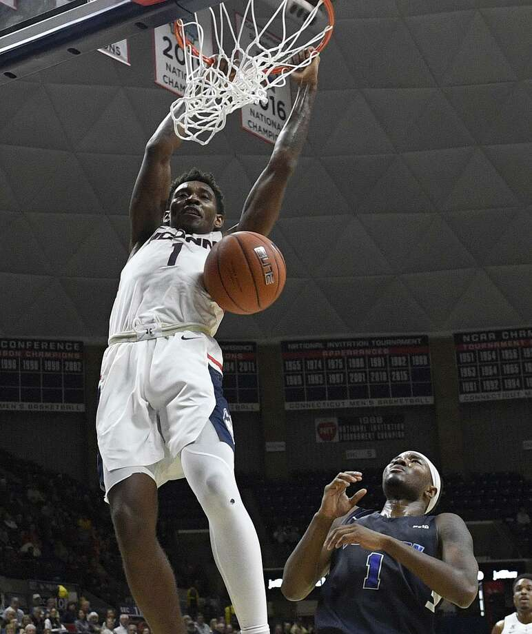 UConn's Christian Vital dunks over Southern Connecticut's Isaiah McLeod during the first half of an exhibition game on Friday in Storrs. Photo: Jim Michaud / Associated Press / JIM MICHAUD