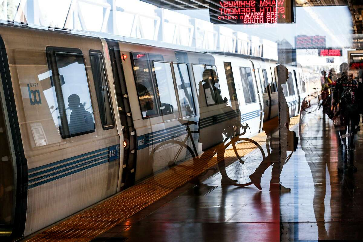 Passengers are seen through a reflection at MacArthur BART Station on Friday, November 2, 2018 in Oakland, Calif.