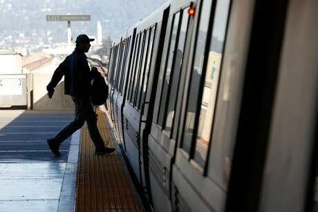 A passenger runs onto a train at MacArthur BART Station in Oakland. Photo: Amy Osborne / Special To The Chronicle
