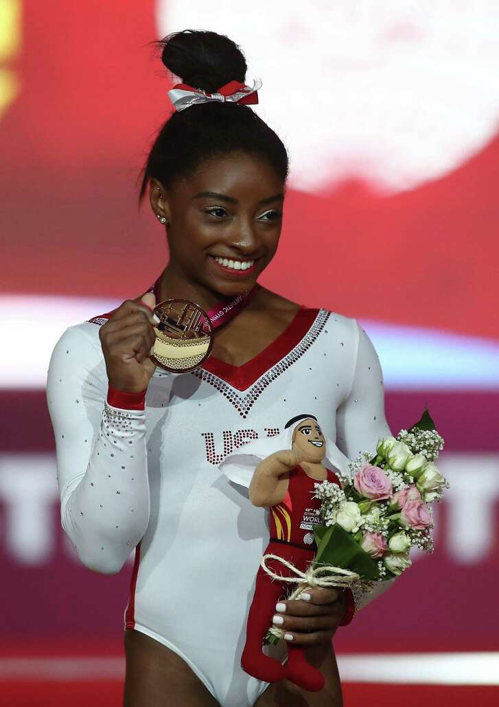 Simone Biles shows off her gold medal from Friday's vault at the world championships in Doha, Qatar.