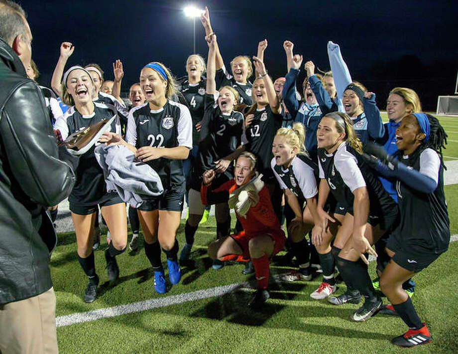 Members of the Lewis and Clark Community College women's soccer team celebrate after receiving the championship plaque after beating rival Southwestern Illinois College 5-1 Friday night in the Central District Tournament final at McKendree University's Leemon Field in Lebanon. Photo: Jan Dona | For The Telegraph