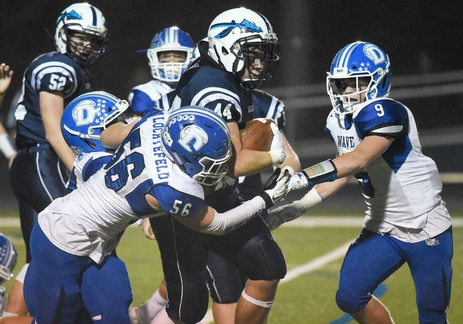 Darien's John Lochtefeld (56) tackles Wilton's Tyler Previte (44) with help from Sam Wilson (9) on Friday. Photo: Dave Stewart / Hearst Connecticut Media / Contributed Photo / Greenwich Time Contributed