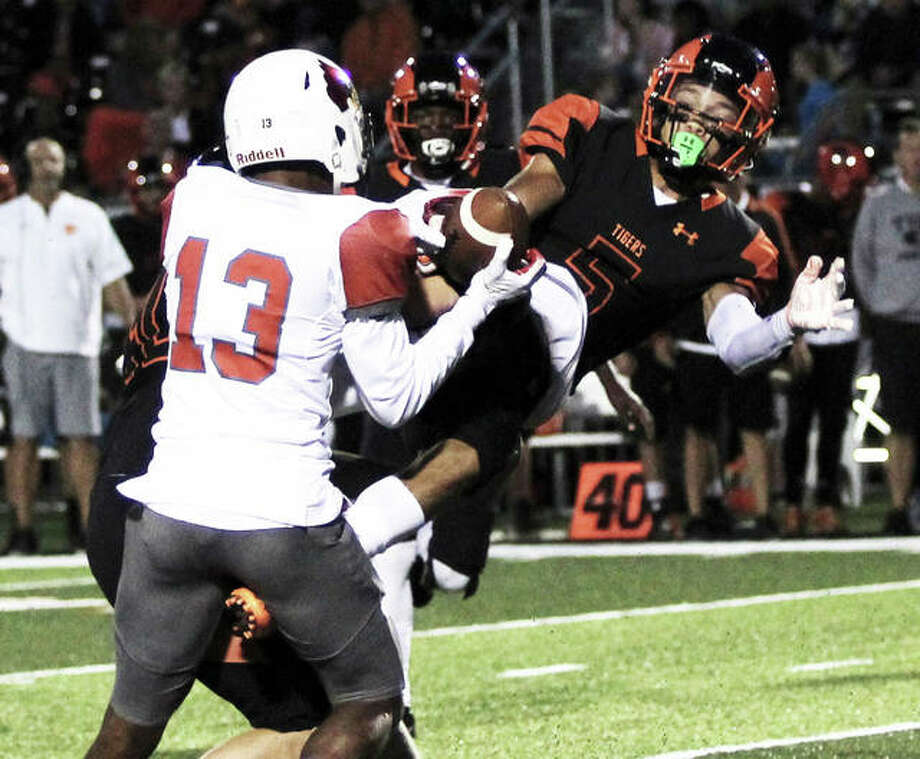 Edwardsville's Jalen Cooper (right) makes a play on the football while Alton's Moory Woods (13) makes a catch in heavy traffic over the middle in a Southwestern Conference game Sept. 21 in Edwardsville. The Tigers are back on their home turf at 5 p.m. Saturday for a second-round Class 8A playoff game against West Aurora. Photo: Greg Shashack / The Telegraph