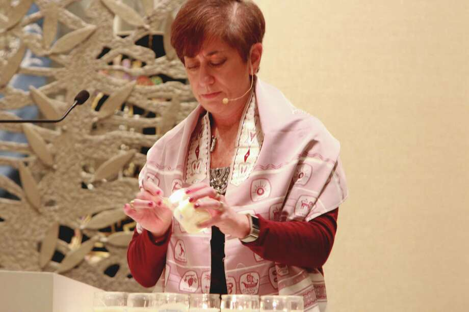 During a Shabbat service Friday, Greenwich Reform Synagogue Cantor Harriet Dunkerley lights 11 candles — one for each person killed in the Tree of Life Synagogue shooting on Oct. 27. Photo: Hannah Dellinger / Hearst Connecticut Media