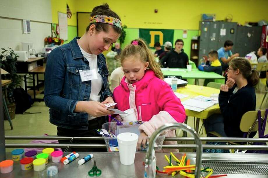 Hannah Baker, 17, left, and Chloe Grimm, 8, right, collect art supplies during Big Brothers Big Sisters' Teaming Up with YOUth after-school program on Thursday, Oct. 18 at H. H. Dow High School. (Katy Kildee/kkildee@mdn.net)