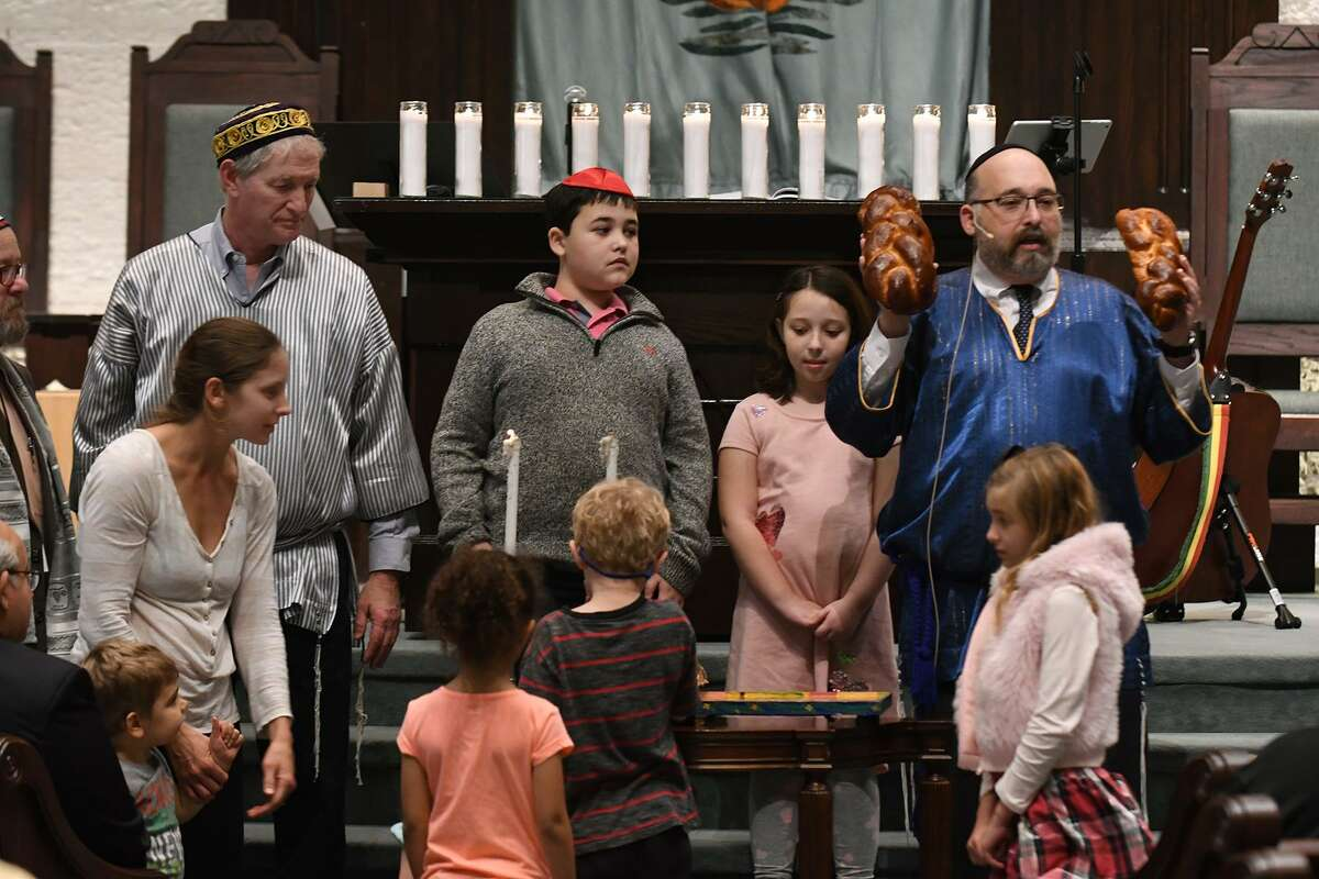 Rabbi Jonathan Siger, right, with bread in hand, with his son Azi, 11, center, delivers his Blessing of the Sabbath to his congregation and guests at the Solidarity Service held at Congregation Jewish Community North in Spring on Nov. 2, 2018.