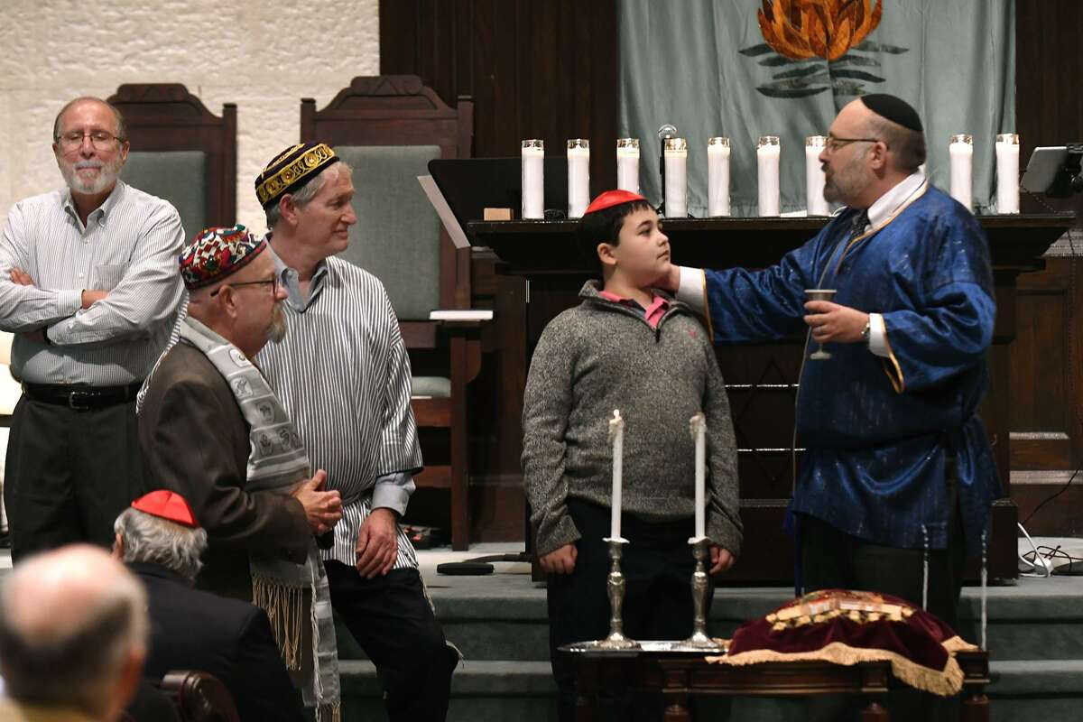 Rabbi Jonathan Siger, from right, with his son Azi, 11, delivers his Blessing of the Children message to his congregation and guests at the Solidarity Service held at Congregation Jewish Community North in Spring on Nov. 2, 2018.