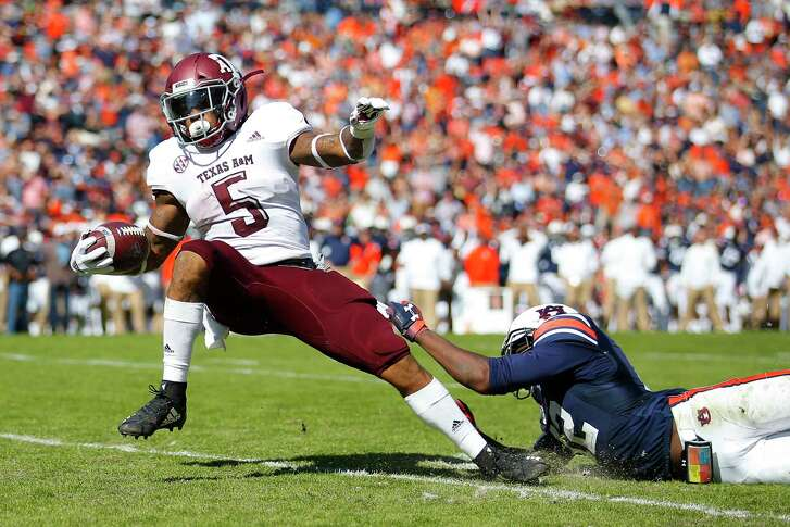 Texas A&M running back Trayveon Williams (5) breaks the tackle of Auburn defensive back Jamel Dean (12) to score a touchdown during the first half of an NCAA college football game, Saturday, Nov. 3, 2018, in Auburn, Ala. (AP Photo/Todd Kirkland)
