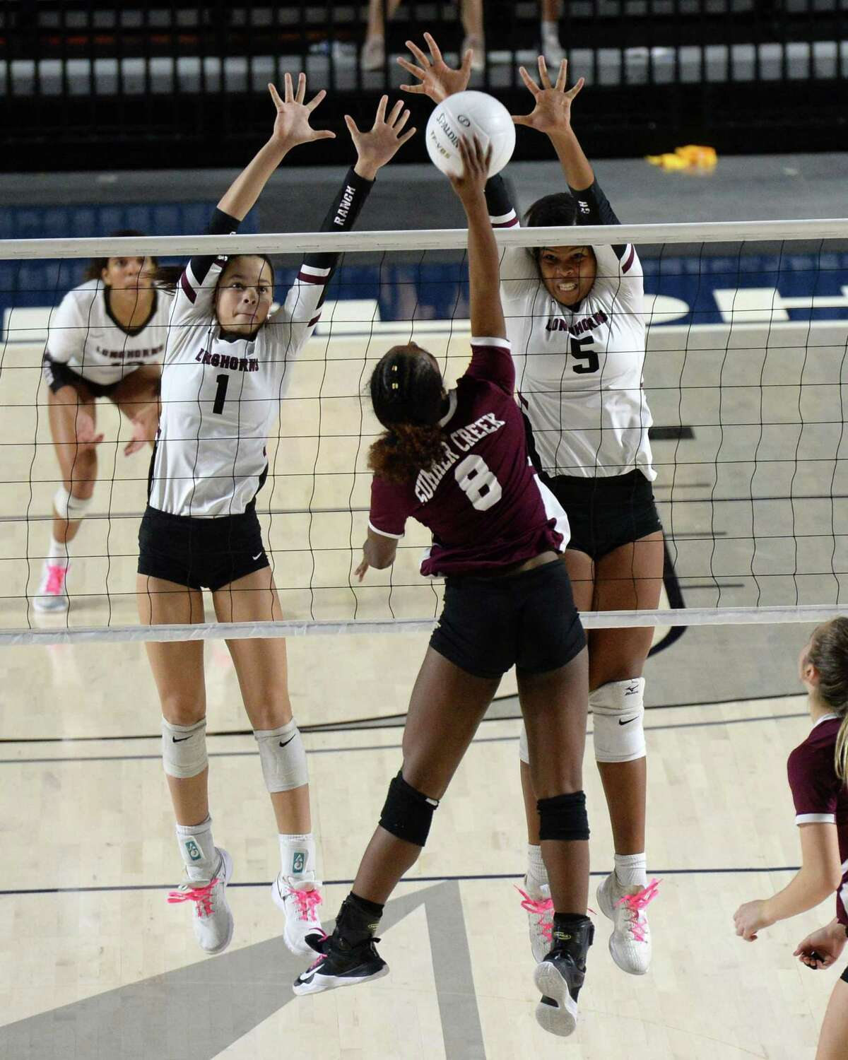 Alexandra Tennon (1) and Kennedy Prince (5) of George Ranch try to block the shot made by Amiya Matthews (8) of Summer Creek in the third set of a Class 6A Region III Area-round playoff volleyball match between the George Ranch Longhorns vs Summer Creek Bulldogs on Friday, November 2, 2018 at Delmar Fieldhouse, Houston, TX.