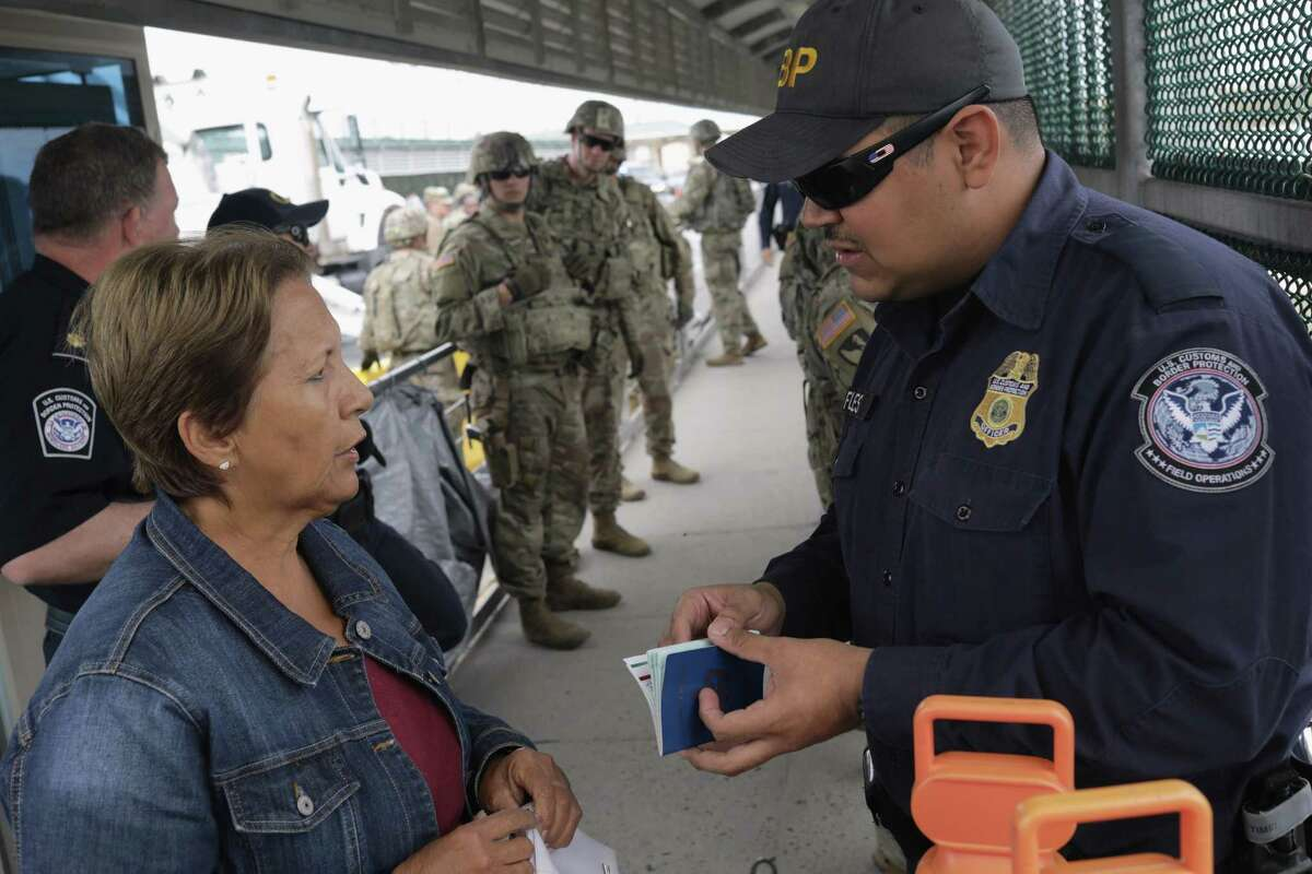 HIDALGO, TX - NOVEMBER 02: U.S. A Customs and Border Protection speaks with a Cuban asulum seeker as newly arrived U.S. Army troops watch at the international bridge with Mexico on November 2, 2018 in Hidalgo, Texas. U.S. President Donald Trump ordered the troops to the border to bolster security at points where an immigrant caravan may attempt to cross in upcoming weeks. (Photo by John Moore/Getty Images)