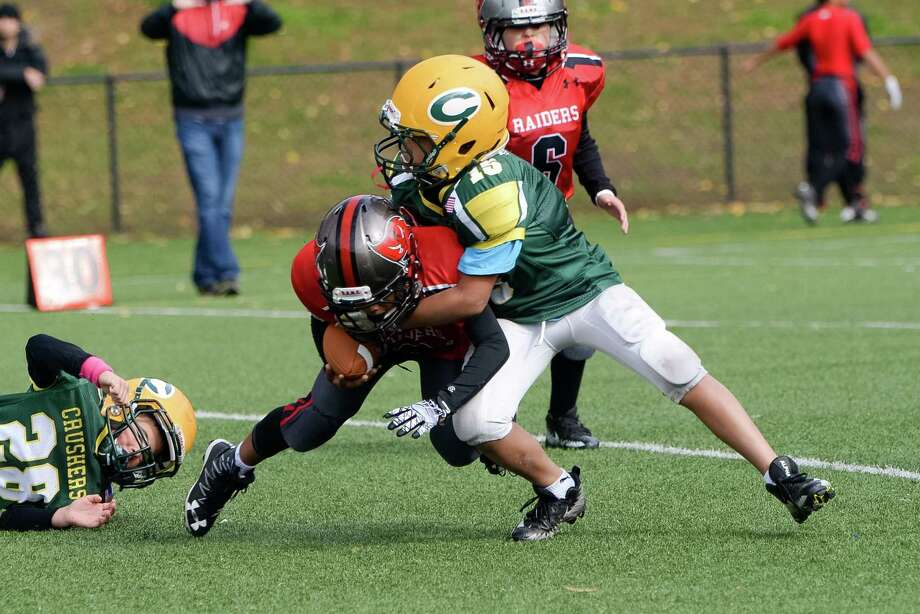 Bantam Crusher Braden Raybuck (15) wraps up a Raiders runner. Photo: Contributed Photo / Greenwich Time Contributed
