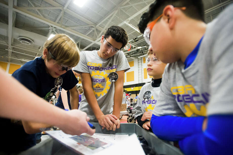 Calvary Baptist Academy students Charlie Tomko, 13, center, Jack Parrillo, 11, second from right, and Mario Salses, 11, right, make a gameplan with players on another team during the Great Lakes Bay Region FTC Qualifier robotics competition on Saturday, Nov. 3, 2018 at Bullock Creek High School. (Katy Kildee/kkildee@mdn.net) Photo: (Katy Kildee/kkildee@mdn.net)