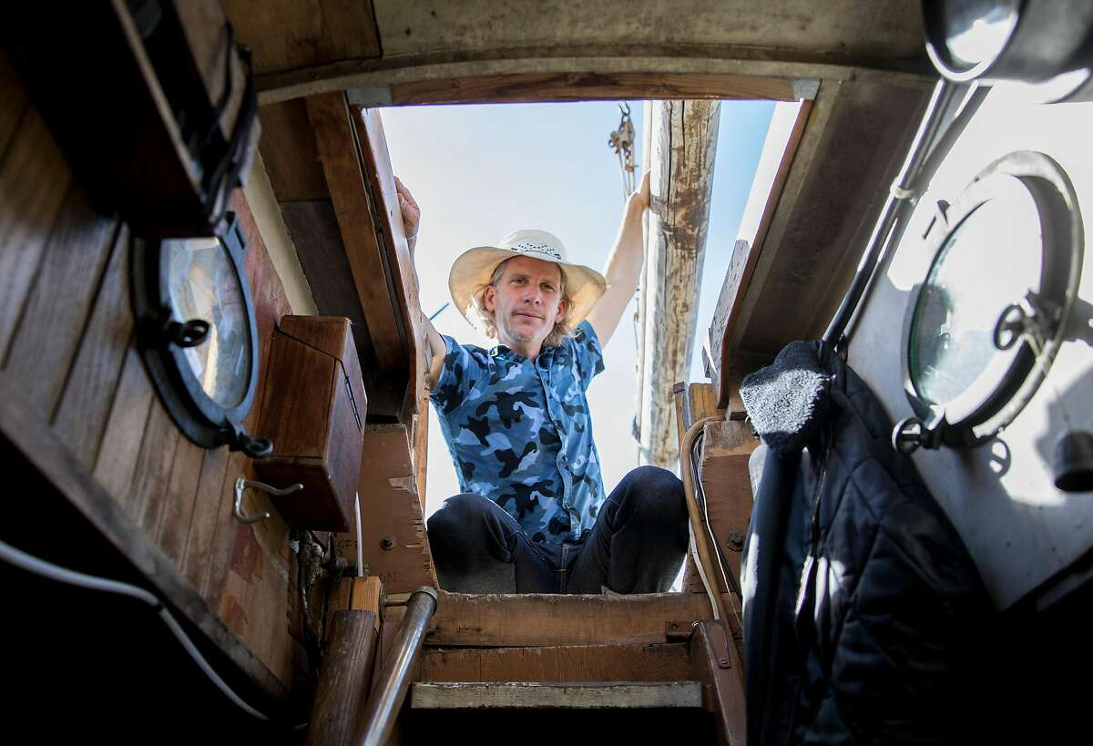 Former anchor-out resident Alden Bevington looks down into the living quarters of Greg Baker's boat, the CA Marcy, while on the waters of Richardson Bay in Sausalito, Calif. Saturday, Nov. 3, 2018.