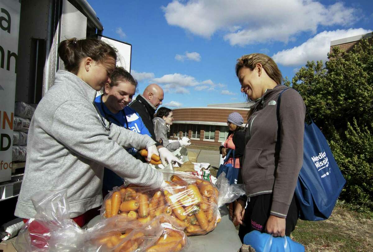Sacred Haert Nursing student Johanna Klimaszewski, left, hands out some carrots to Kendy Lopez during St. Vincent?'s fourth annual Medical Mission at Home at Cesar Batalla School in Bridgeport, Conn., on Saturday, Nov. 3, 2018. More than 300 volunteers helped to provide free medical care to members of the community. Some of the free services provided for adults includes medical exams, vaccinations, podiatry services, haircuts, food provided by the Connecticut Food Band as well as shoes and coats.