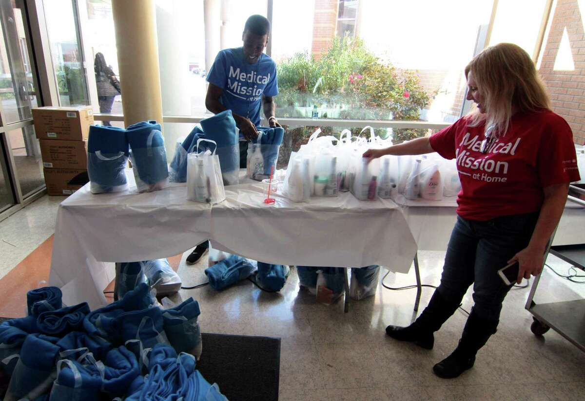 Danielle Swift, Chief Communications and Marketing Officer at St. Vincent?'s, at right, checks out the bags of personal care products given out during the hospital's fourth annual Medical Mission at Home at Cesar Batalla School in Bridgeport, Conn., on Saturday, Nov. 3, 2018. More than 300 volunteers helped to provide free medical care to members of the community. Some of the free services provided for adults includes medical exams, vaccinations, podiatry services, haircuts, food provided by the Connecticut Food Band as well as shoes and coats.