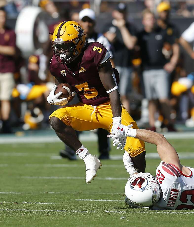 Arizona State running back Eno Benjamin steps over a would-be Utah tackler Saturday. Photo: Rick Scuteri / Associated Press