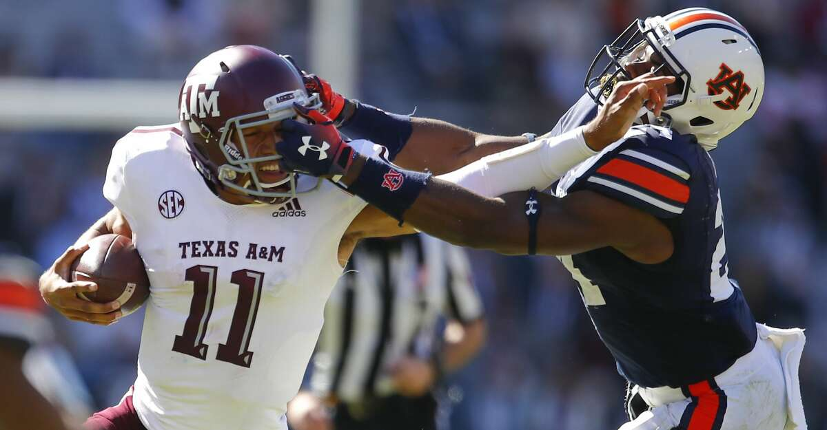 Auburn defensive back Daniel Thomas (24) grabs the facemask of Texas A&M quarterback Kellen Mond (11) during the second half of an NCAA college football game, Saturday, Nov. 3, 2018, in Auburn, Ala. Thomas was called for a penalty on the play. (AP Photo/Todd Kirkland)