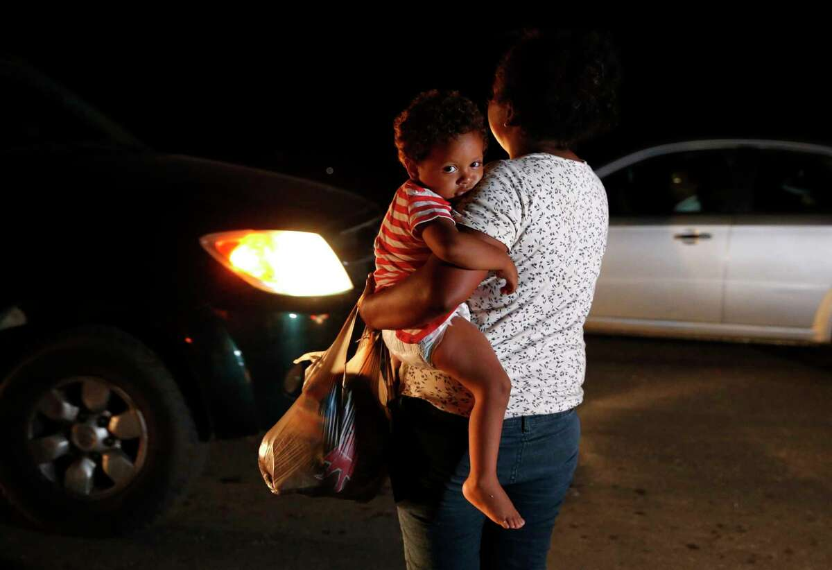Honduran migrant Luz Padilla Valverde, carrying her child, begs for contributions of one peso (about 5 cents) from passing drivers as a thousands-strong caravan of Central Americans hoping to reach the U.S. border stops for the night Nov. 1, 2018, in Matias Romero, Oaxaca state, Mexico. (AP Photo/Rebecca Blackwell)