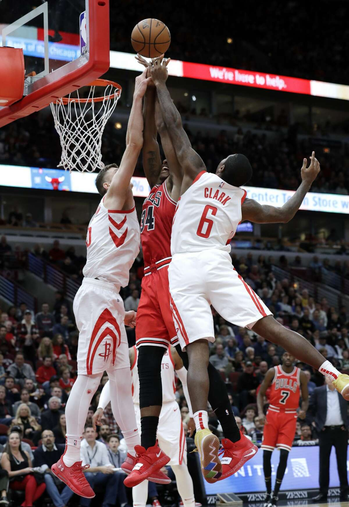 Houston Rockets forward/center Isaiah Hartenstein, left, and forward Gary Clark, right, block a shot by Chicago Bulls center Wendell Carter Jr., center, during the second half of an NBA basketball game Saturday, Nov. 3, 2018, in Chicago. (AP Photo/Nam Y. Huh)