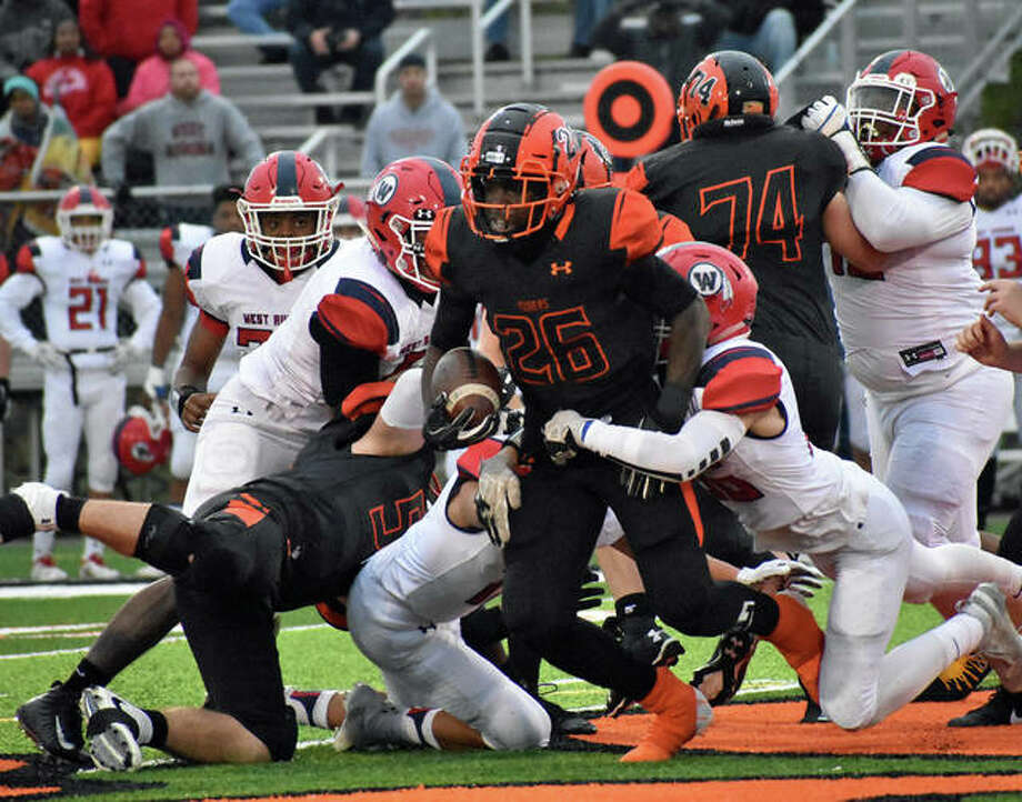 Edwardsville running back Justin Johnson (No. 26) looks for running room in a crowd of players against West Aurora in the second round of the IHSA Class 8A postseason. Photo: Matt Kamp/Intelligencer